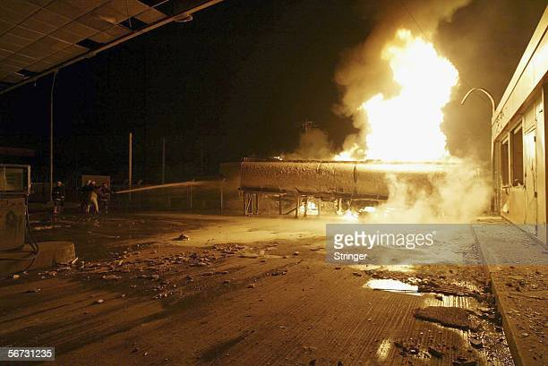 Iraqi firemen battle flames rising from a gas station after a car bomb exploded nearby on February 2 2006 in Baghdad Iraq The blast killed at least...