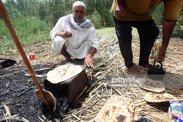 Iraqi fishermen cook unleavened bread on an open fire on the shores of the alHuwaiza marshes northern Amara 420 km south of Baghdad on June 13...