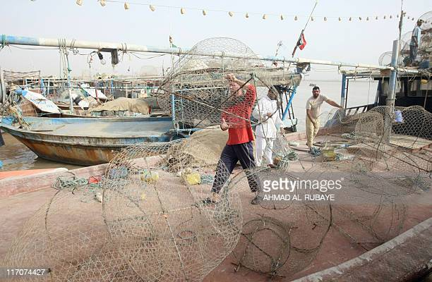 Iraqi fishermen prepare their nets in the port of Iraq's southernmost Faw peninsula on the border with Iran on June 11 2011 Like the fish they net...