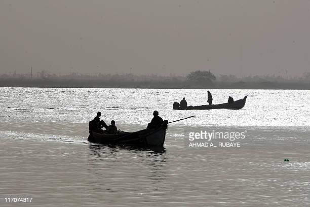 Iraqi fishermen ride their boats in the waters of Iraq's southernmost Faw peninsula on the border with Iran on June 11 2011 Like the fish they net...