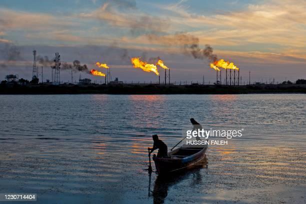 Iraqi fishermen row their boat across flare stacks burning at the Nahr Bin Omar field, north of the southern Iraqi port of Basra, on January 21, 2021.