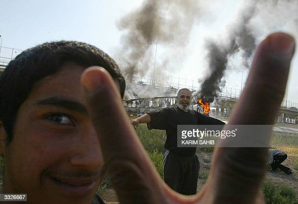 Iraqi flashes the V for victory sign as another celebrates near a burning truck attacked by insurgents on the road leading to Baghdad's International...