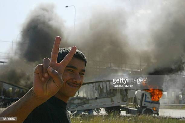 Iraqi flashes the V for victory sign near a burning truck attacked by insurgents on the road leading to Baghdad's International Airport 10 April 2004...