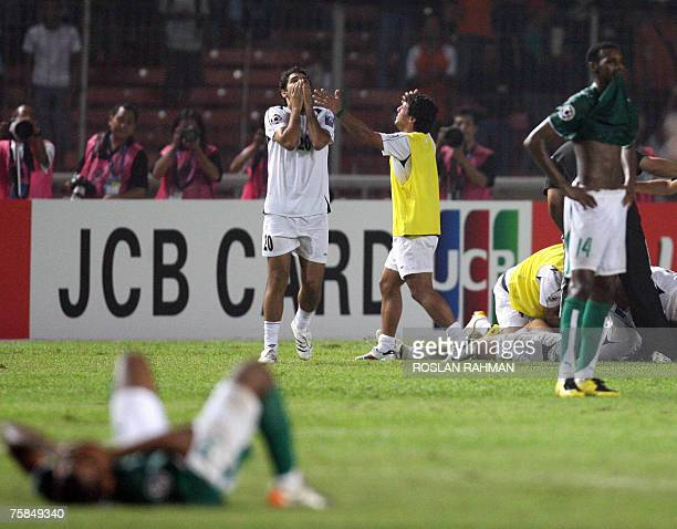 Iraqi football defender Nabeel Abbas expresses relief while Saudi Arabia players reacts in disappoinment after Iraq'S victory in the Asian Football...