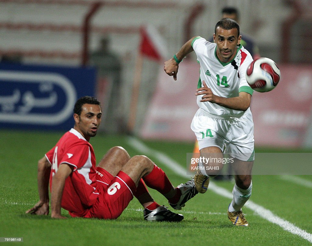 Iraqi football player Haidar Abdul Amir (R) runs for ball while his Jordanian opponent Awad Raghed falls on the ground during a friendly match between the two countries' national teams in Dubai 24 January 2008. The game ended in a 1-1 draw.