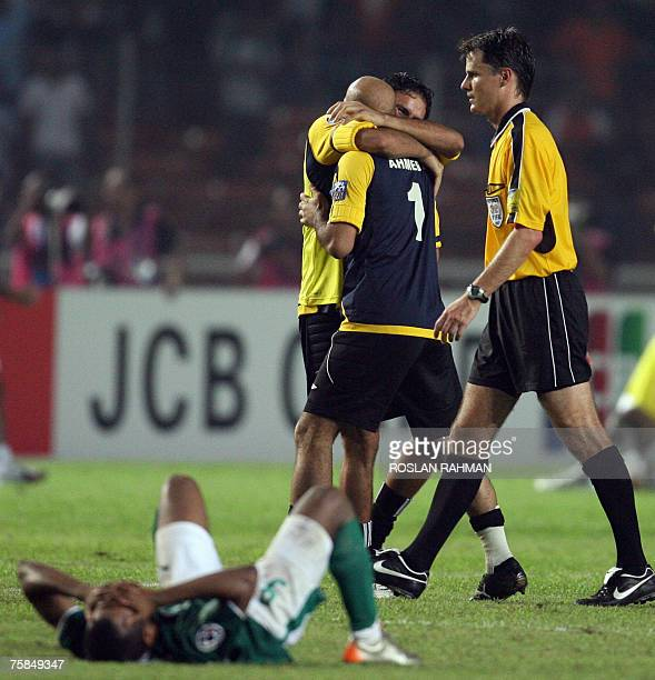 Iraqi football players hug each other while a Saudi Arabian player lies on the field in disappoinment after Iraq's victory in the Asian Football Cup...