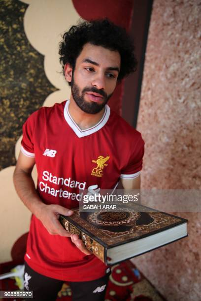 Iraqi footballer Hussein Ali who plays for the Iraqi AlZawraa FC and is a lookalike of Liverpool's Egyptian forward Mohamed Salah carries a copy of...
