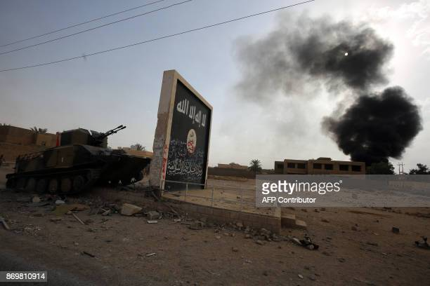 Iraqi forces and members of the Hashed alShaabi advance next to a wall bearing the Islamic State group flag as they enter the city of alQaim in...