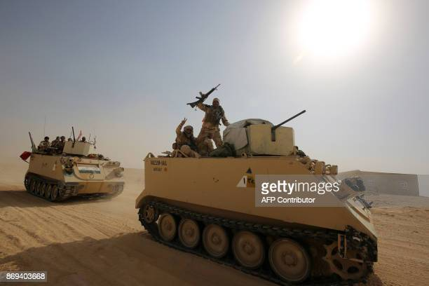 TOPSHOT Iraqi forces and members of the Hashed alShaabi advance towards the city of alQaim in western Anbar province on the Syrian border as they...