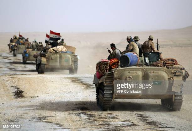 Iraqi forces and members of the Hashed alShaabi advance towards the city of alQaim in western Anbar province on the Syrian border as they fight...