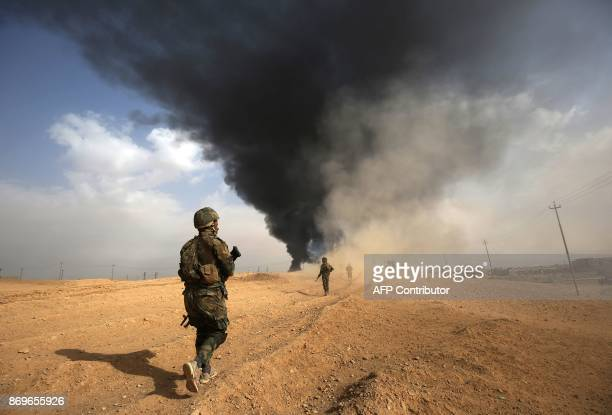 Iraqi forces and members of the Hashed al-Shaabi advance towards the city of al-Qaim, in Iraq's western Anbar province near the Syrian border as they...