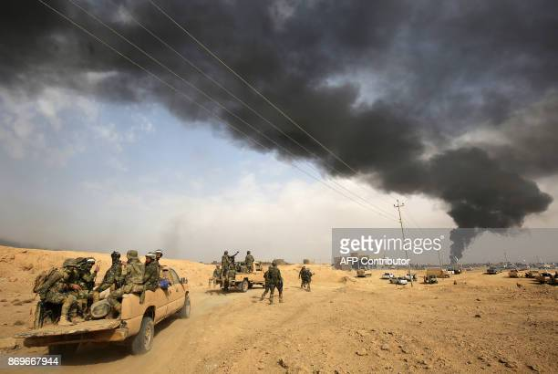 Iraqi forces and members of the Hashed alShaabi advance towards the city of alQaim in Iraq's western Anbar province near the Syrian border as they...
