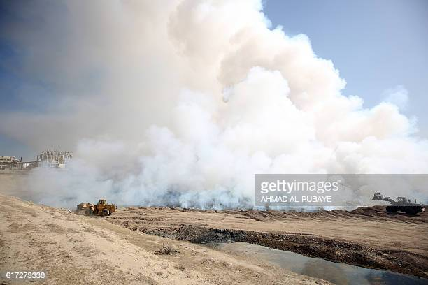 Iraqi forces attempt to extinguish the flames after Islamic State group jihadists torched Mishraq sulphur factory near the Qayyarah base about 30...