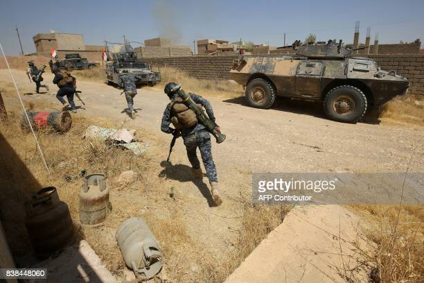 TOPSHOT Iraqi forces backed by the Hashed alShaabi advance through Tal Afar's alWahda district during an operation to retake the city from the...