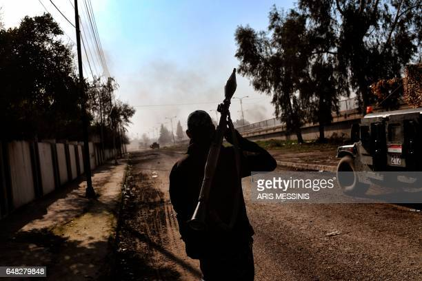 TOPSHOT Iraqi forces clash with Islamic State group fighters in Mosul on March 5 during an offensive to retake the western parts of the city from the...
