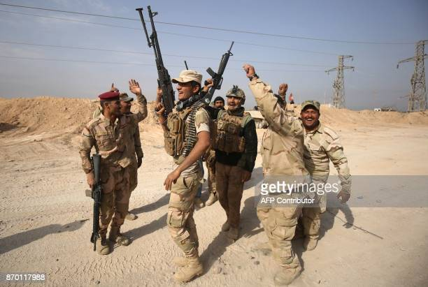 Iraqi forces dance on November 4, 2017 near the Syrian border after recapturing the border town of Qaim, west of Anbar, from the Islamic State group...