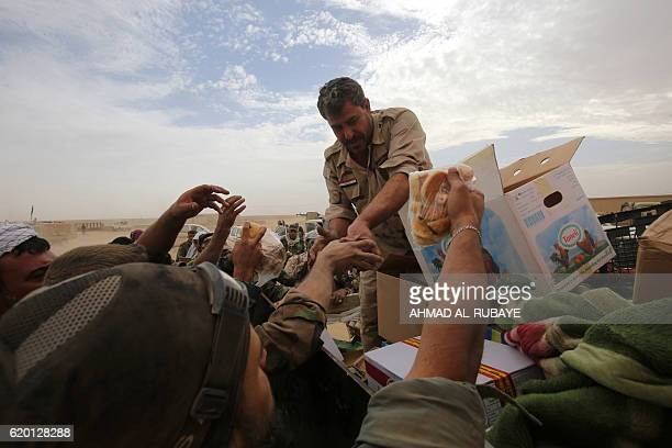 TOPSHOT Iraqi forces distribute food as they enter the village of Abu Shuwayhah south of jihadistheld Mosul on November 1 during the ongoing...