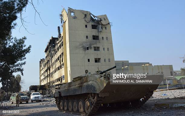 Iraqi forces drive a tank next to AlSalam hospital in the alWihdah neighbourhood after recapturing the area from Islamic State group jihadists on...