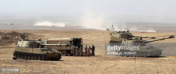 TOPSHOT Iraqi forces fire artillery shells towards the nearby village of Zalhafa from their position on the outskirts of the village of alKhuwayn...