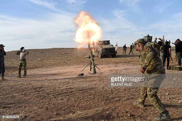 TOPSHOT Iraqi forces fire mortar shells towards positions of Islamic State group jihadists on October 21 on the frontline on the outskirts of...