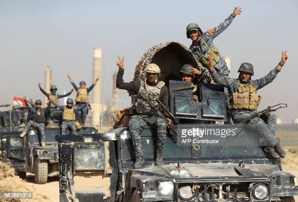 Iraqi forces flash the sign for victory while driving past an oil production plant as they head towards the city of Kirkuk during an operation...