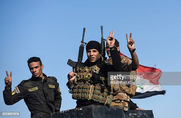 TOPSHOT Iraqi forces flash the sign of victory as they drive their vehicle on November 3 2016 near Gogjali which lies on the eastern edge of Mosul...