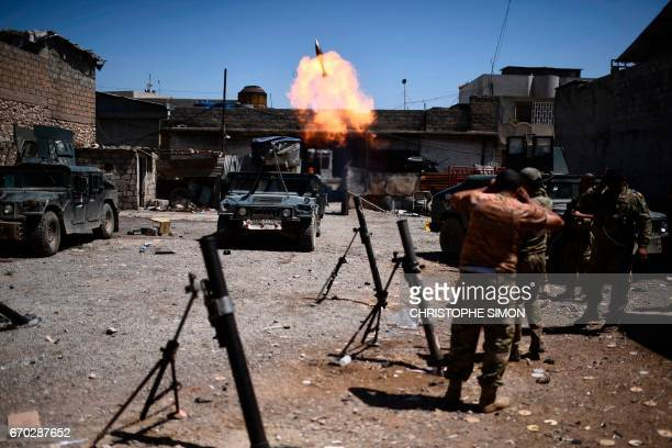 TOPSHOT Iraqi forces from the elite Rapid Response Division fire mortars towards Islamic State group positions during their advance in western Mosul...