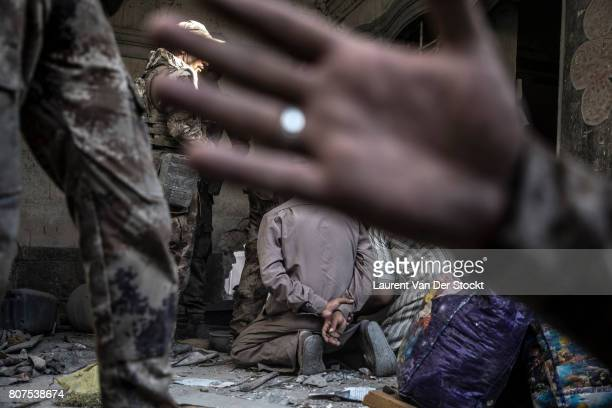 Iraqi forces interrogate two men they suspect of being affiliated with the Islamic State in alNuri mosque complex on June 29 in Mosul Iraq They were...