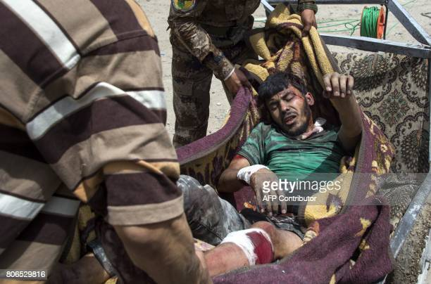 Iraqi forces members carry an injured man on a blanket as they evacuate civilians in the Old City of Mosul on July 3 2017 during an ongoing offensive...