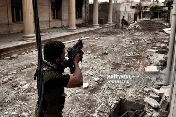 Iraqi forces members fire from outside the museum towards Islamic State jihadists' positions in west Mosul on March 11 2017 during the ongoing battle...