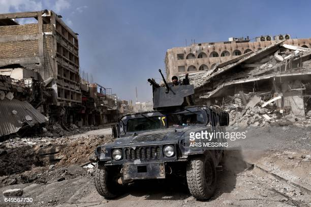 TOPSHOT Iraqi forces patrol in a street in west Mosul as they advance inside the city during fighting against Islamic State group's fighters on March...
