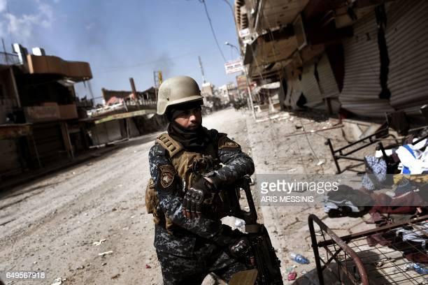 Iraqi forces patrol in a street in west Mosul as they advance inside the city during fighting against Islamic State group's fighters on March 8 2017...
