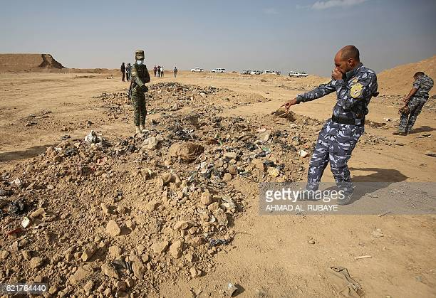 Iraqi forces point at a mass grave they discovered in the Hamam alAlil area on November 7 2016 after they recaptured the area from Islamic State...
