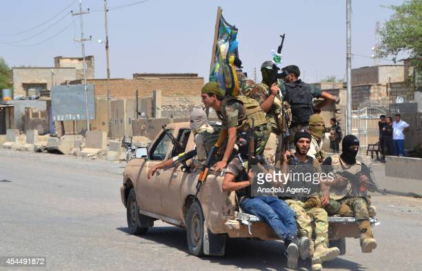 Iraqi forces ride on a pickup following clashes of Iraqi forces for seizing the village of Sulaiman Bek Iraqi forces ride on a pickup following...