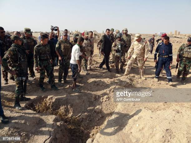 Iraqi forces search the site of a suspected mass grave containing the remains of victims of the Islamic State group near the former al bakara...