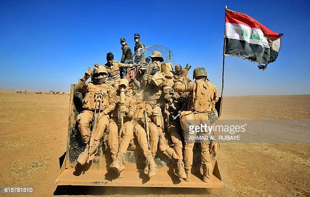 TOPSHOT Iraqi forces sit in the back of a vehicle as troops advance through the desert on the banks of the Tigris river northeast of the main staging...