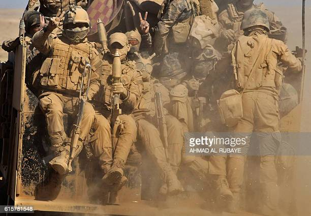 Iraqi forces sit in the back of a vehicle as troops advance through the desert on the banks of the Tigris river northeast of the main staging base of...