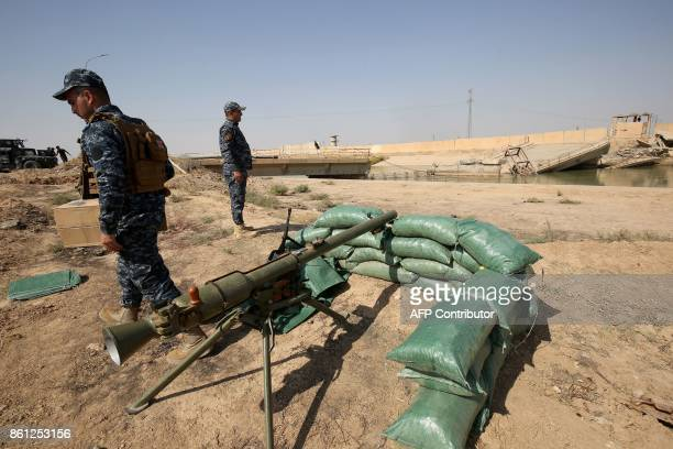 Iraqi forces stand on a river bank across from Kurdish peshmerga positions on October 14 on the southern outskirts of Kirkuk. Thousands of Iraqi...