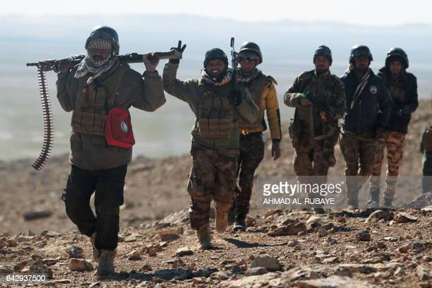 TOPSHOT Iraqi forces supported by the Hashed alShaabi paramilitaries advance near the village of Sheikh Younis south of Mosul after the offencive to...