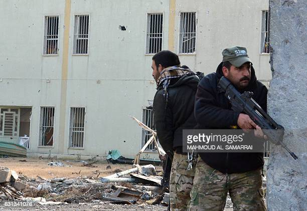 Iraqi forces take a position behind a wall while securing an area next to AlSalam hospital in the alWihdah neighbourhood in Mosul after recapturing...