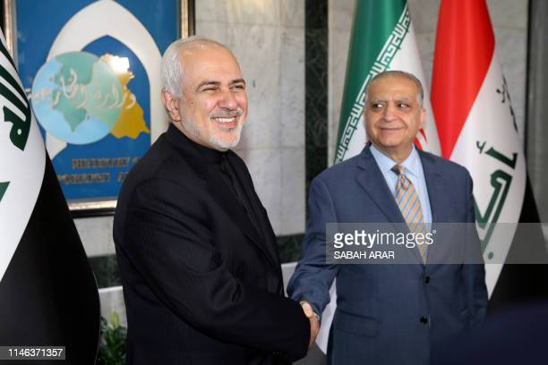 Iraqi Foreign Minister Mohammad Ali alHakim greets Iran's Foreign Minister Mohammad Javad Zarif in Baghdad on May 26 2019