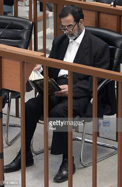 Iraqi former President Saddam Hussein reads in the Koran during final arguments of his trial in the heavily fortified Green Zone on July 26 2006 in...