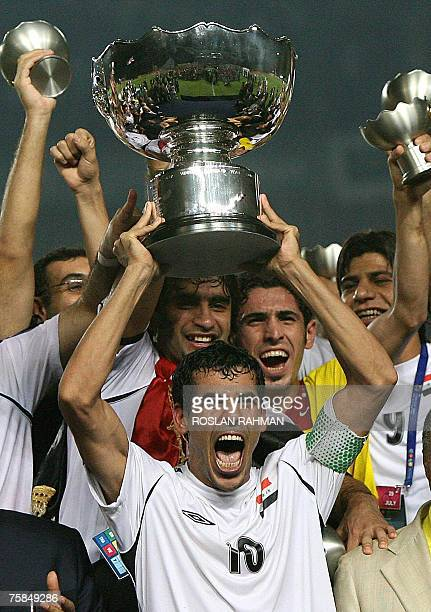 Iraqi forward Younis Mahmoud holds the trophy as he celebrates with teammates at the end of the final match of the Asian Football Cup 2007 at the...