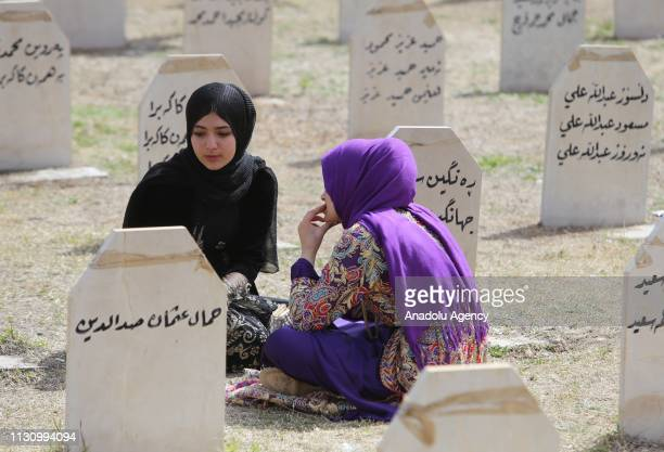 Iraqi girls are seen near gravestones of people, who lost their lives on Halabja chemical attack staged on 16 March 1988, at Halabja cemetery in...