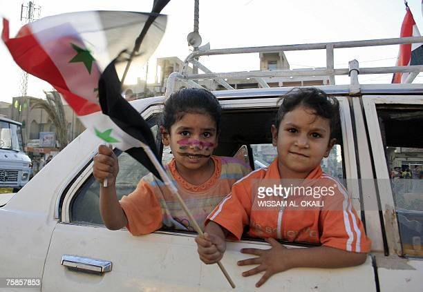 Iraqi girls hold their national flag as they celebrate the victory of their country's football team against Saudi Arabia for the final of the Asian...