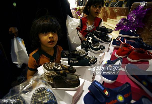 Iraqi girls look at shoes donated to the families of fighters of the Popular Mobilisation units who are supporting the Iraqi government forces in the...