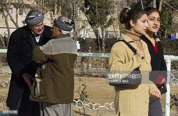 Iraqi girls pass Kurds discussing politics outside Masud Barzani's Kurdish Democratic Party headquarters in the Kurdish city of Suleimaniya 350 kms...