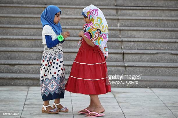 Iraqi girls play outside a mosque in the capital Baghdad after attending prayers on July 28 during the first day of Eid alFitr that marks the end of...