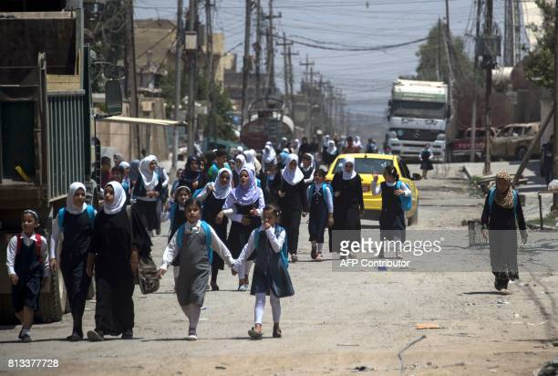 Iraqi girls walk back from school in west Mosul on July 12 2017 after the government declared it had driven the Islamic State group jihadists from...