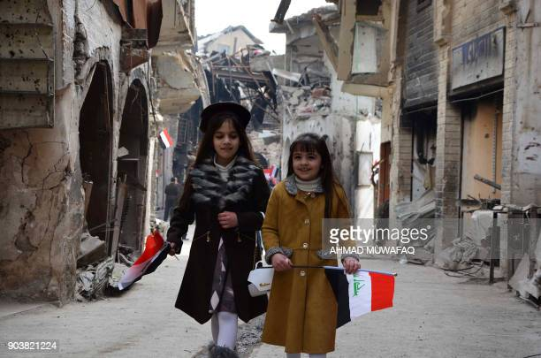 TOPSHOT Iraqi girls walk holding their national flag towards a ceremony for the reopening of the Bab alSaray market in the old city of Mosul on...